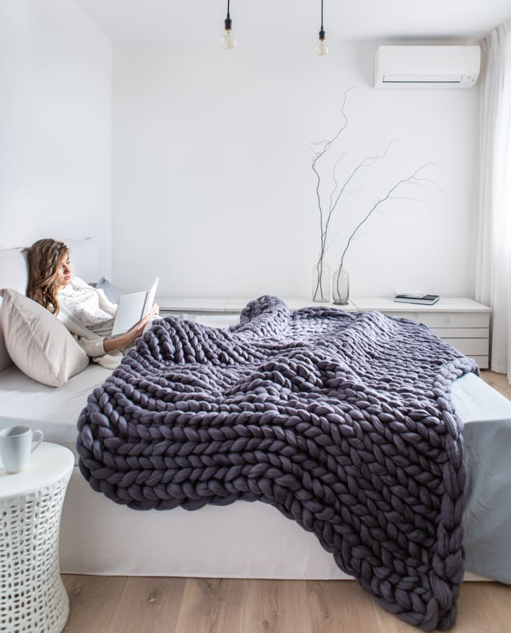 Woman in bed beneath a knit blanket.