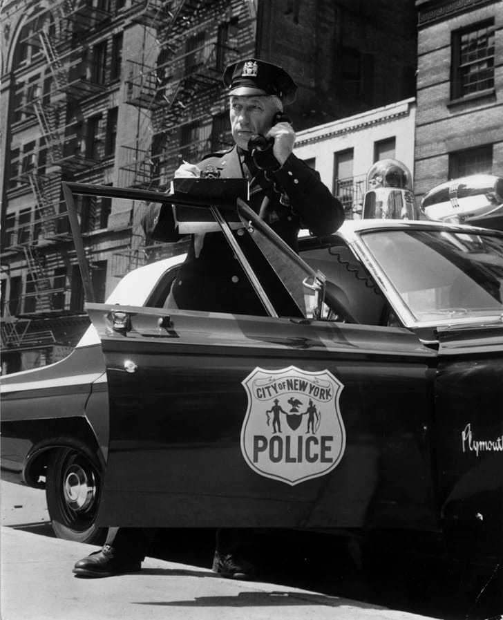 A New York City police officer takes an emergency call from his car in the 1960s