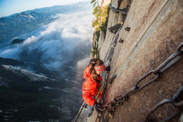 woman climbs mount huashan path