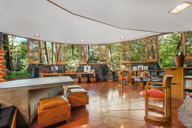 The Sol Friedman House living room is filled with wooden chairs, a stone table, and short shelves.