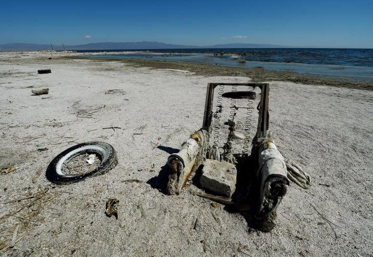 abandoned tire and recliner at salton sea shore