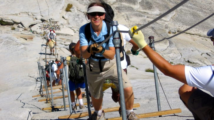 Hikers ascend Half Dome, the granite dome in California's Yosemite Valley, by climbing a steep cable ladder.