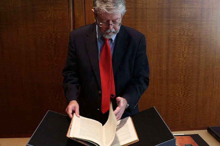A senior specialist for rare books and manuscripts at Christie's holds a copy of former President George Washington's personal copy of the Constitution and Bill of Rights in 2012