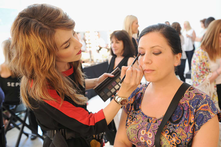 A Sephora employee in uniform applies eyeshadow to another woman seated in a chair
