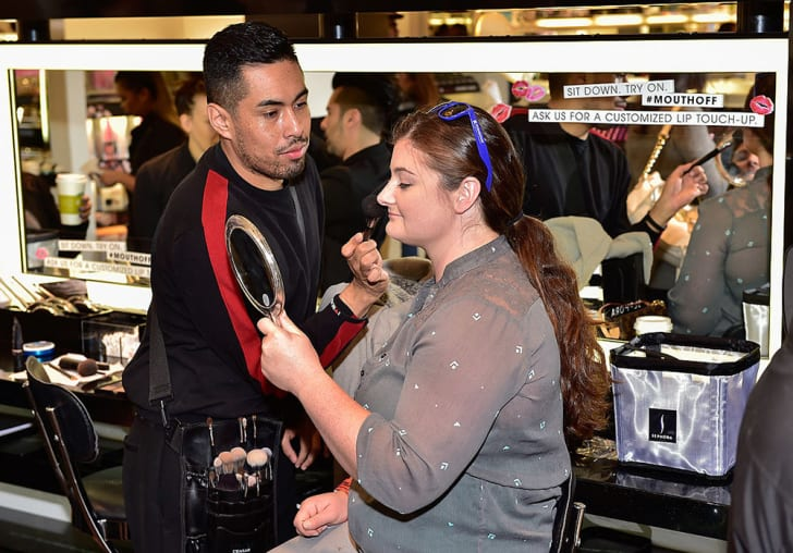 A male Sephora employee applies powder to a seated woman holding a mirror and smiling at her reflection