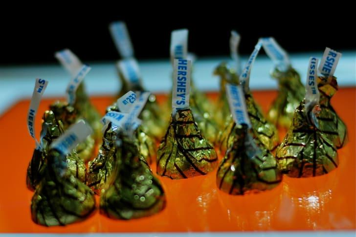 Hershey Kisses on an orange table.