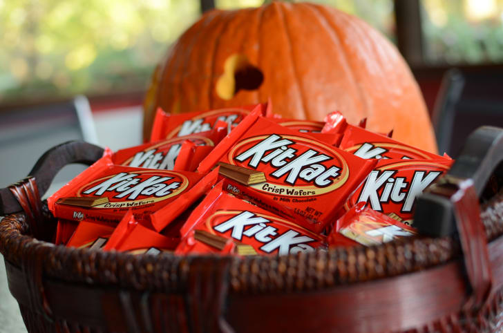 Kit Kats bars in a basket, near a jack o'lantern.