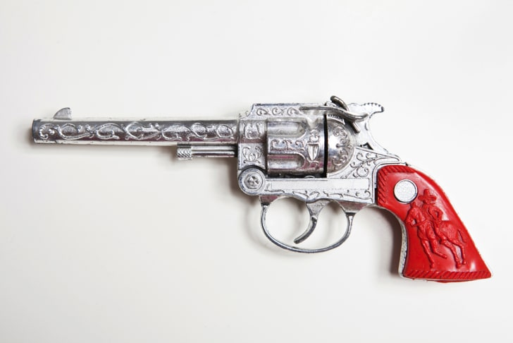 A toy gun with ornate design and red handle