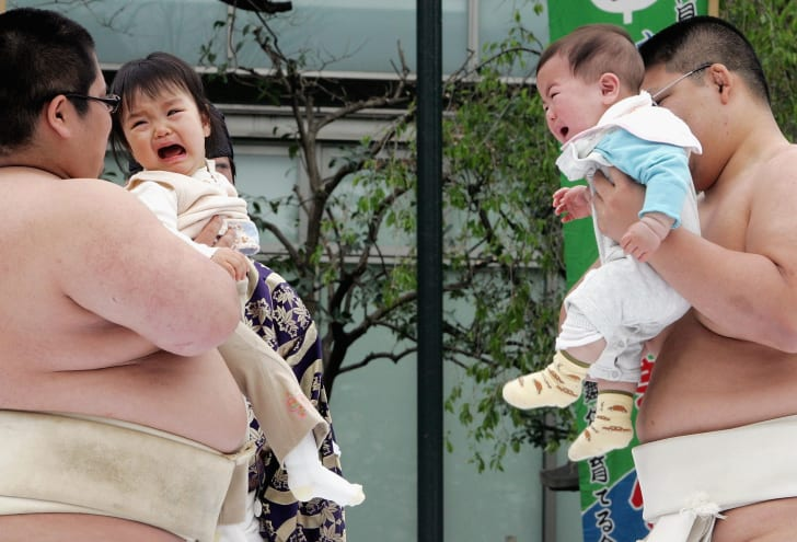 Sumo wrestlers making babies cry (for luck!)