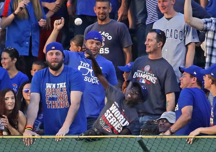 A Cubs fan throws a home run ball back at Wrigley Field