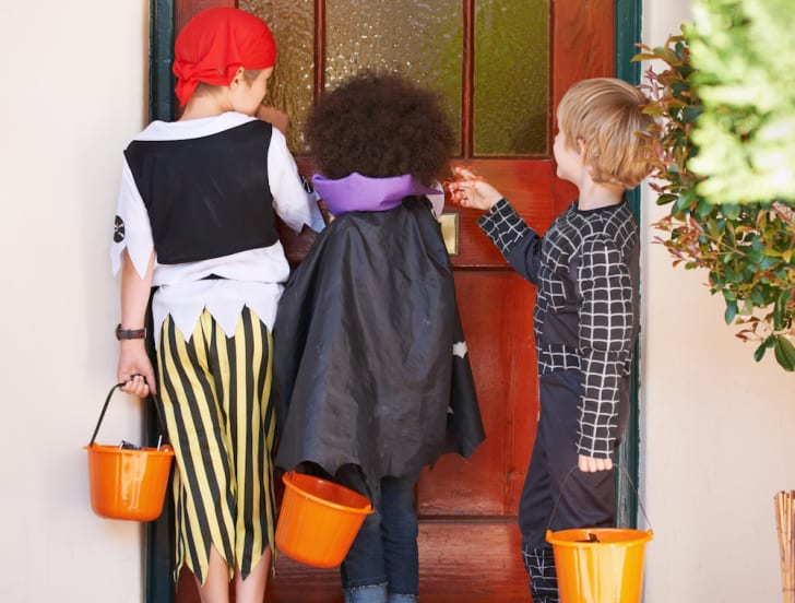 Kids knocking on a door in costume.