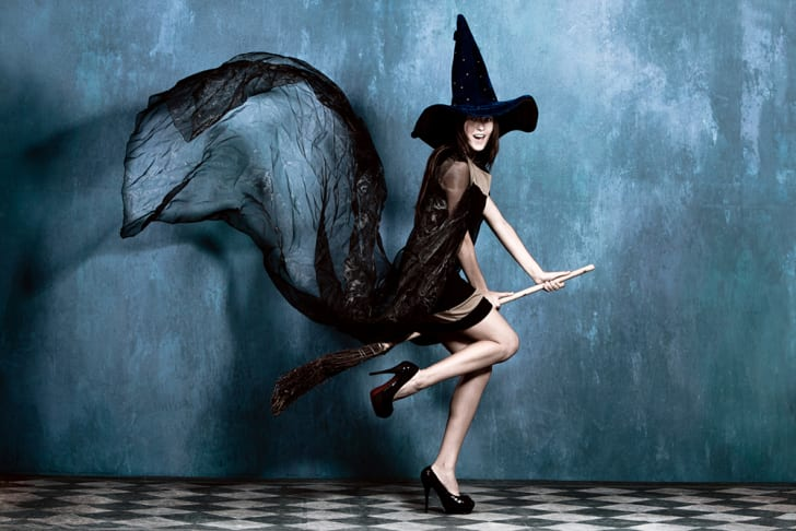 A young woman riding a broom