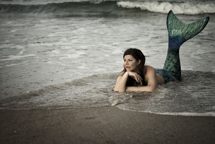 A mermaid looking contemplative on the shore
