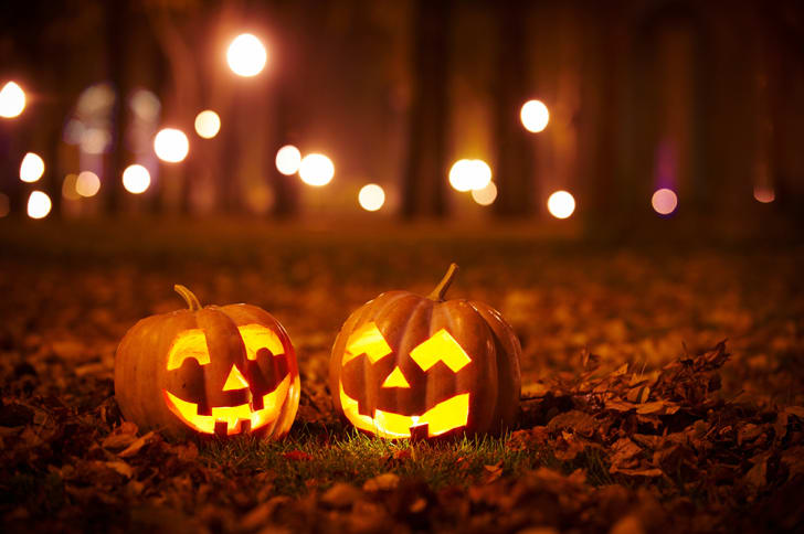 Two carved pumpkins set against a background of glowing woods