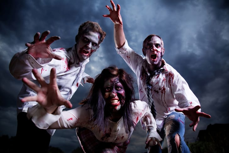 Three zombies reaching for the viewer against a stormy sky