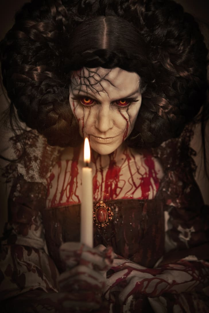 A scary-looking woman covered in blood with a glowing candle in front of her