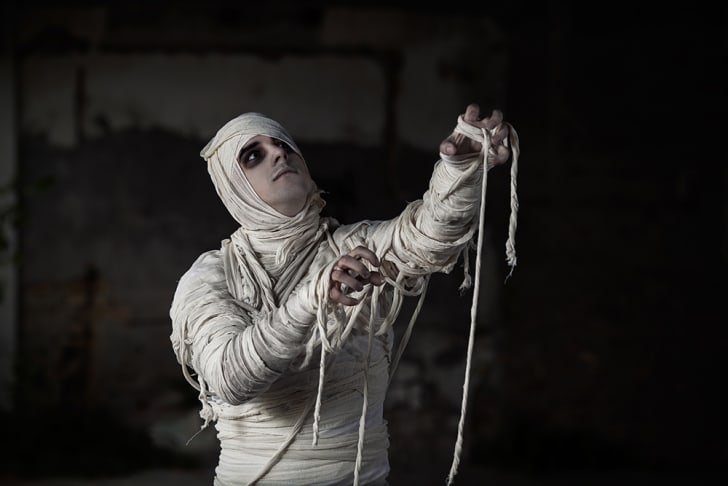 A man dressed up as a mummy and reaching upwards