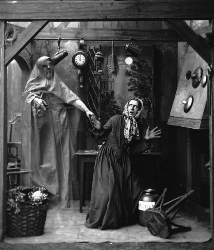 A housewife being scared by a ghost in an old black-and-white photo