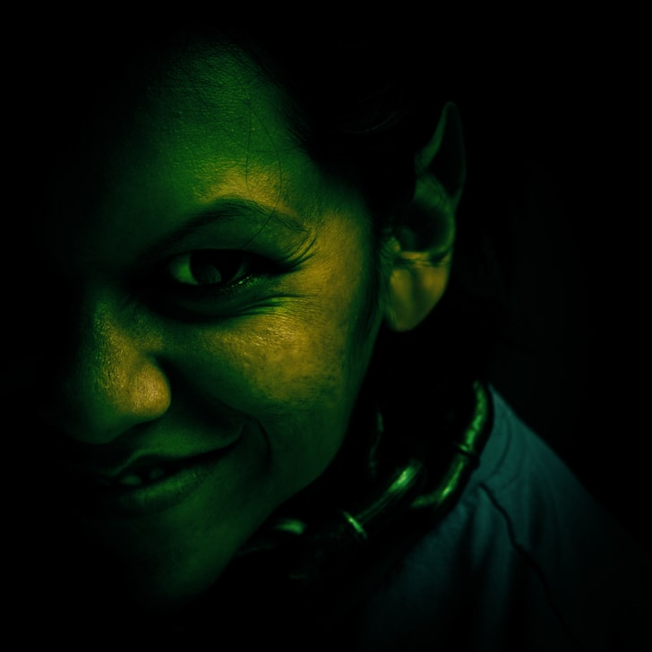 A grinning troll-like woman painted in dark green