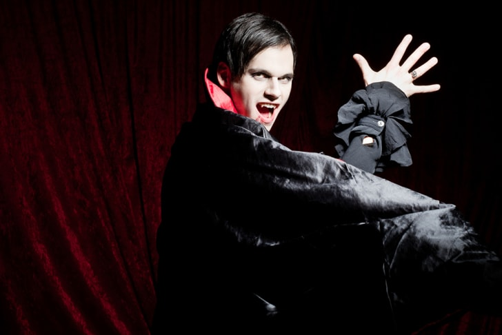 A dramatic male vampire in a velvet cape baring his teeth