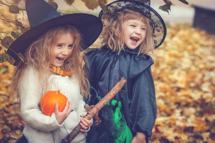 Two adorable blond little girls dressed up like witches for Halloween and grinning, one with a pumpkin