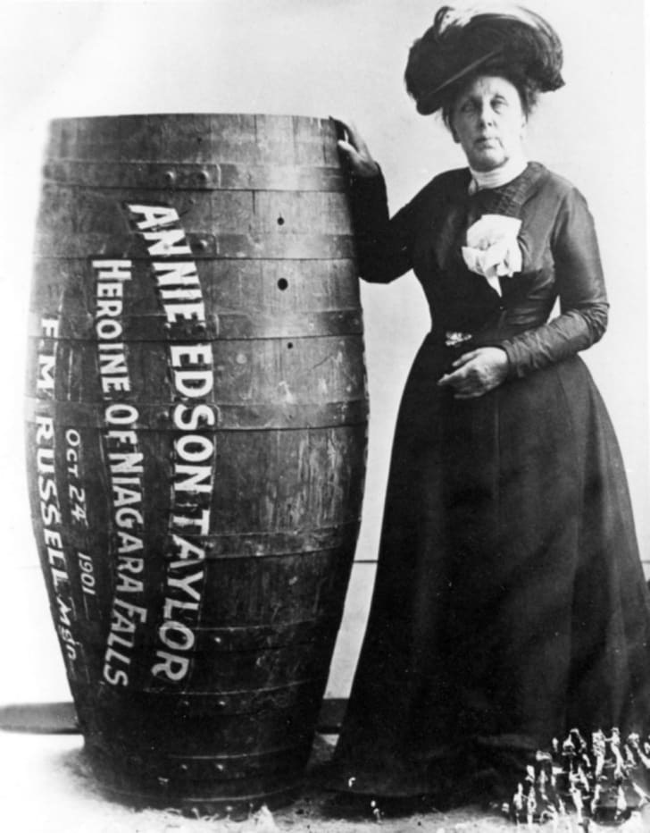 Annie Edson Taylor poses next to the barrel that would carry her over Niagara Falls