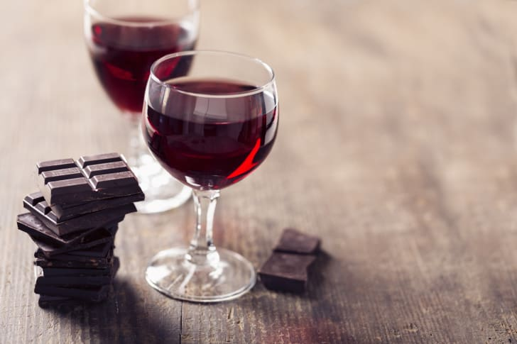 Two classes of red wine on a table with some chocolate.