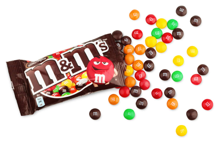 An open bag of plain M&Ms on a white background.