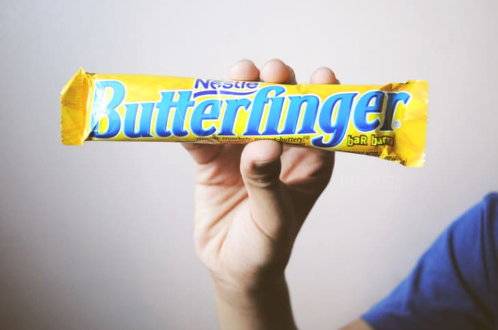 Someone holding up a butterfinger bar.