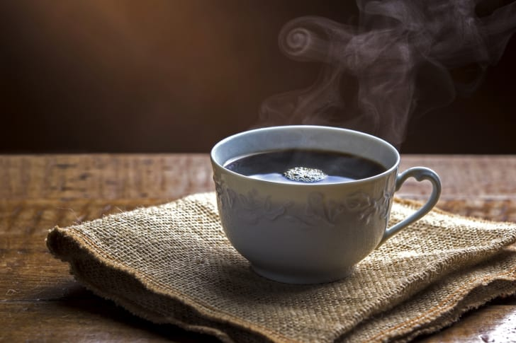A steaming cup of coffee on a piece of burlap.