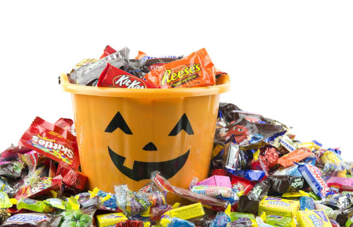 An orange pail with filled with, and surrounded by, Halloween candy.