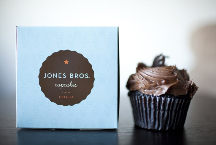 A Jones Bros Sweet and Salty cupcake next to a box.