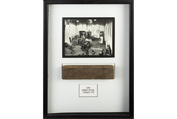 A piece of wood in a frame under a picture of The Beatles