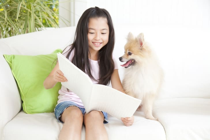 A young girl reads a book to her Pomeranian.