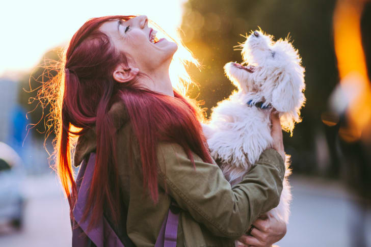 A red haired woman holding a white dog, both laughing.