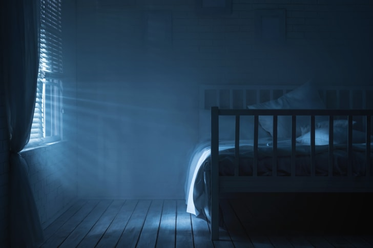 An empty bed in a dark room.