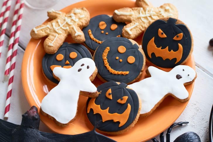 Frosted Halloween cookies shaped like ghosts and pumpkins