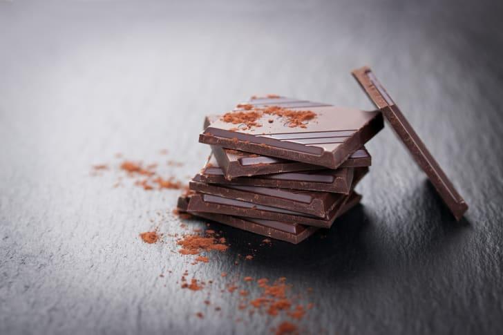 A stack of dark chocolate chunks on a dark stone background