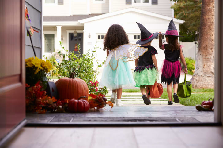 Three children in Halloween costumes trick-or-treating