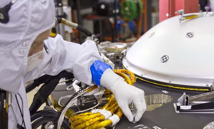 A scientist positions the microchip on the InSight lander.