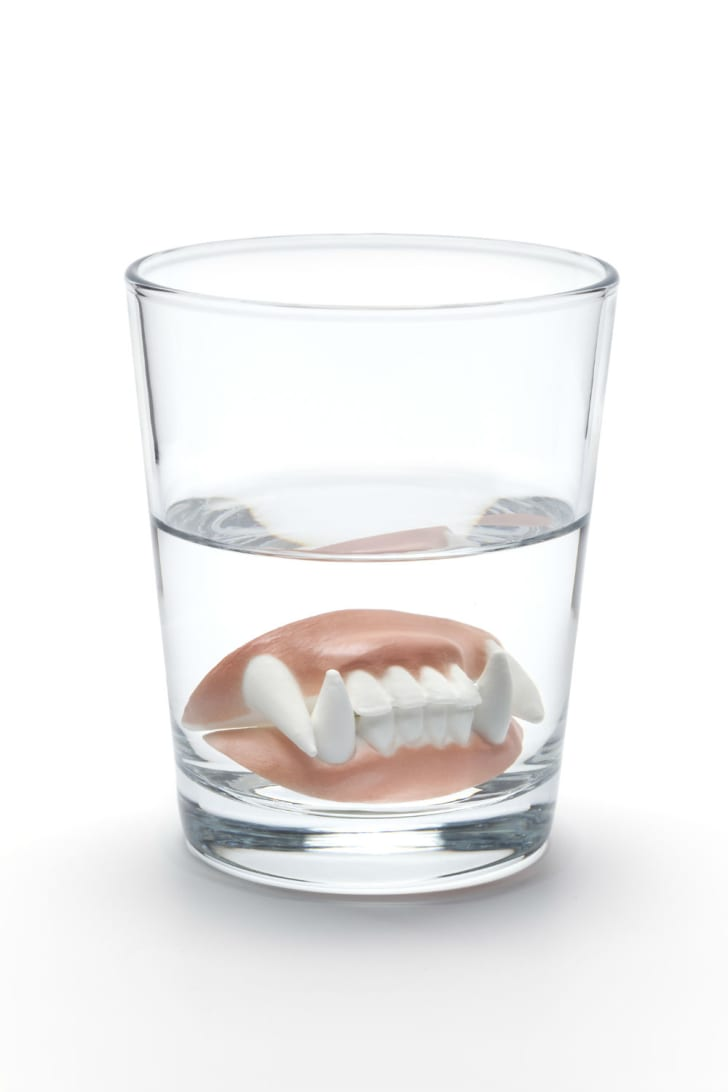Fake vampire teeth sit at the bottom of a water glass