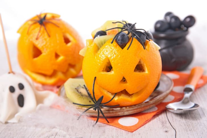 Oranges are cut into Halloween designs and stuffed with treats