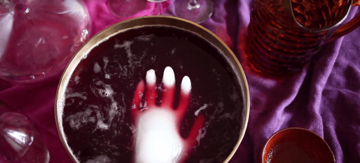 A hand-shaped block of ice floats in a punch bowl