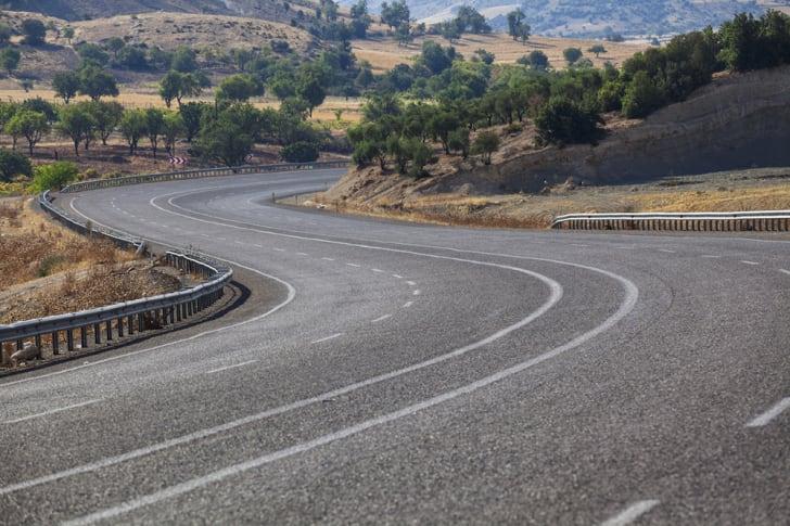 An empty, winding road in an S-shape