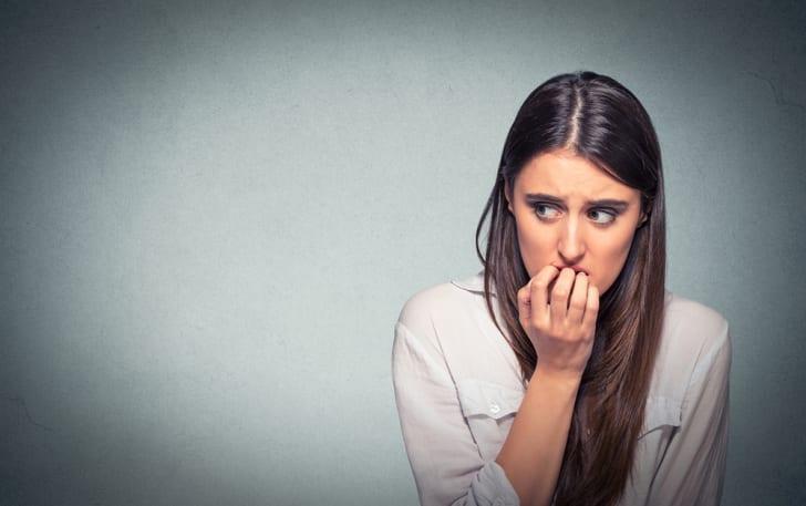 Young nervous woman biting fingernails