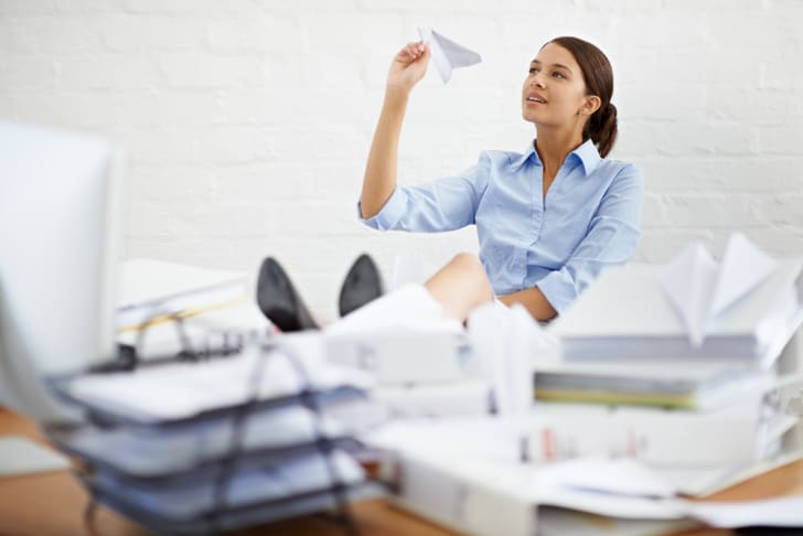 A young woman at a desk surrounded by paperwork, playing with a paper airplane