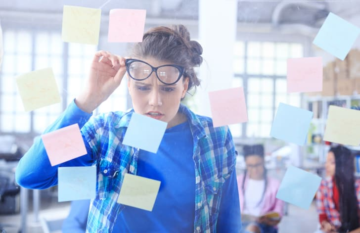 Young woman standing behind a glass wall with post-it notes