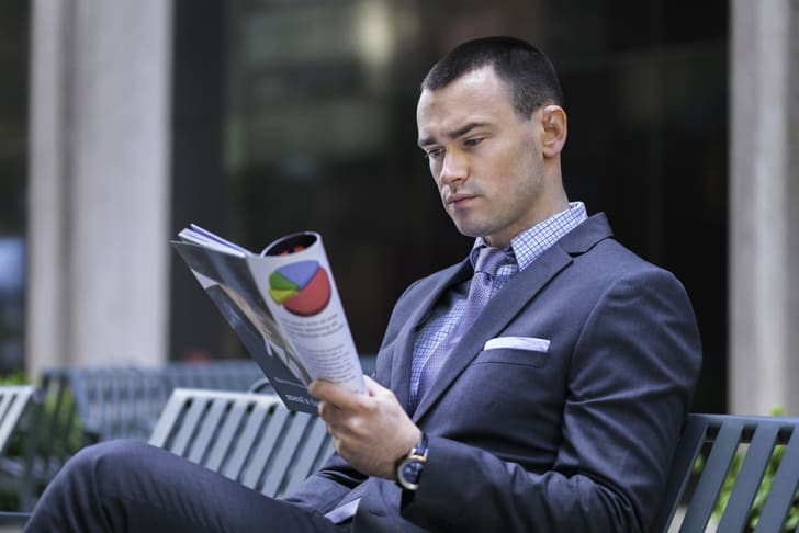 A young man in a business suit reading the paper
