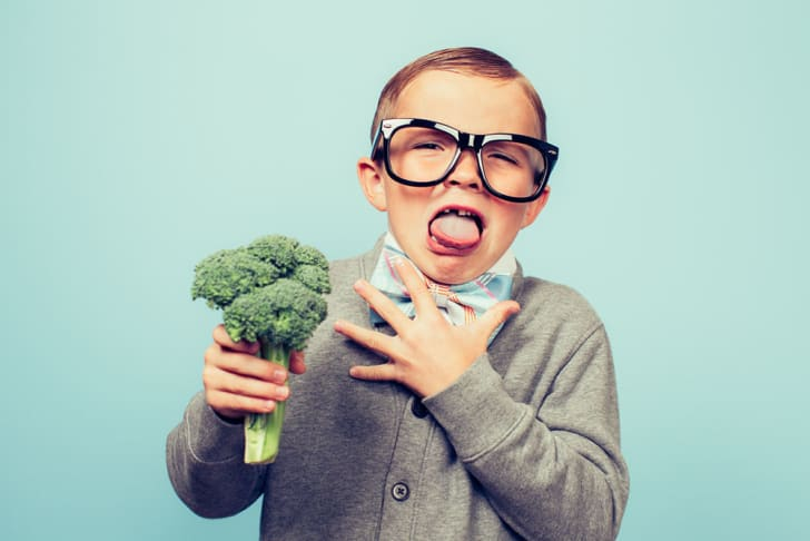 Young boy in oversized black glasses and bow tie with a head of broccoli expressing disgust