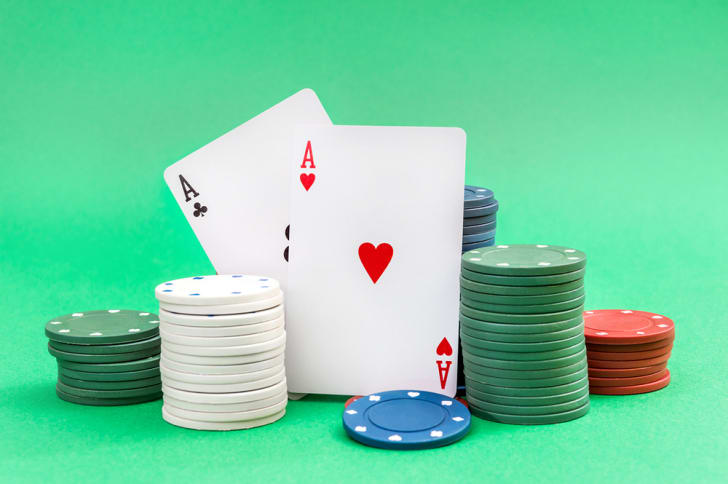 A pair of aces and stacks of poker chips on a green background